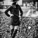Chapeau, robe noire et bottes de cuir