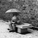 En hiver sur un banc avec un livre et sous un parapluie