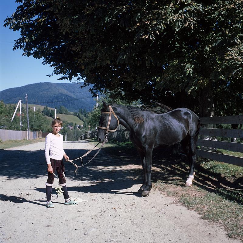[Ukraine 2019] Cette petite fille est sortie de sa maison avec son cheval au bout d'une longe. Elle escaladera la barrière à droite de la photo pour monter dessus avant de partir au galop. La scène me semblait surréaliste !