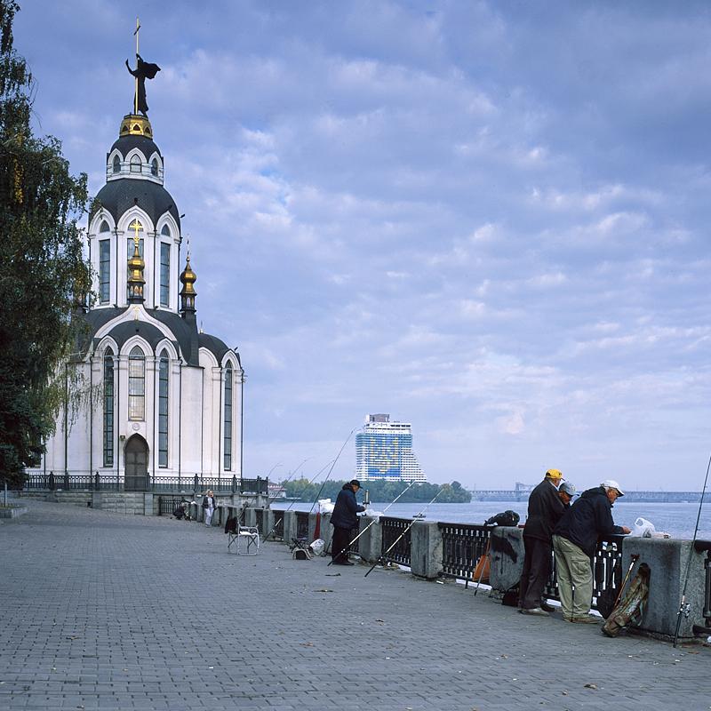 Le Dniepr est le plus important fleuve d'Ukraine et l'un des plus grands d'Europe. Dnipro fut construite sur ses rives, lesquelles ont été aménagées en promenades piétonnes. Dès les premières heures du matin, de nombreux ukrainiens viennent y pêcher. S'il est probables qu'ils vivent de cette pêche, il n'en reste pas moins vrai que c'est aussi l'occasion de se voir entre amis. On distingue au loin l'hôtel Parus, désaffecté depuis des années. Sa façade repeinte aux couleurs du pays symbolise l'appartenance forte de Dnipro à l'Ukraine et non à la Russie dont les troupes ne sont qu'à quelques centaines de kilomètres de là. Ça n'empêche pas la ville d'être particulièrement paisible et agréable à visiter.
